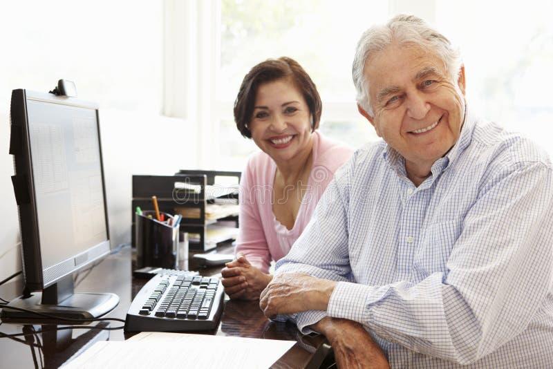 Pares hispánicos mayores que trabajan en el ordenador en casa imagenes de archivo