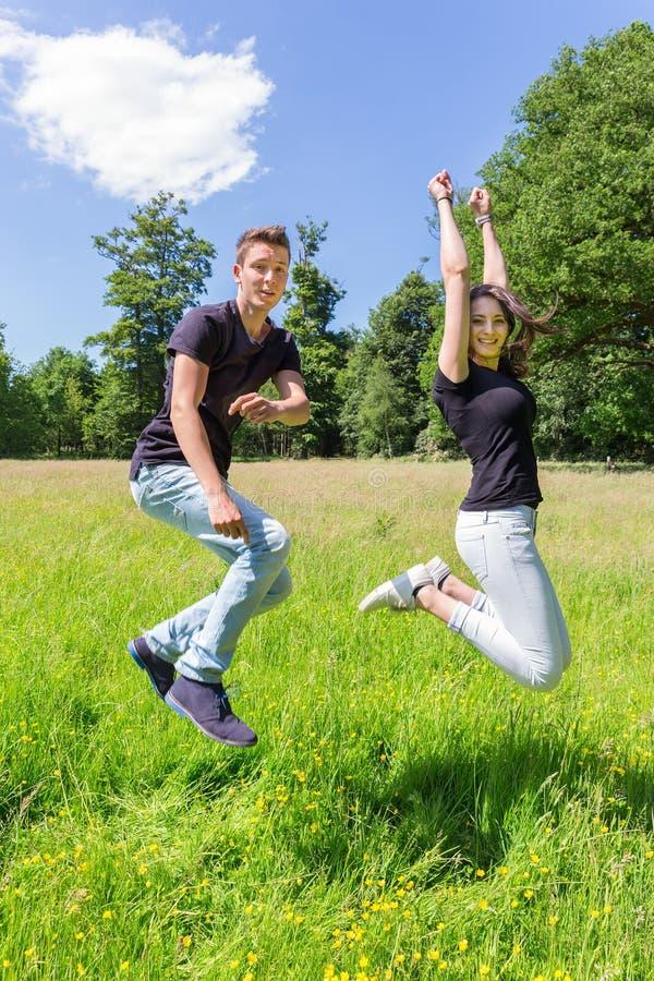 Pares holandeses jovenes que saltan en prado verde imágenes de archivo libres de regalías