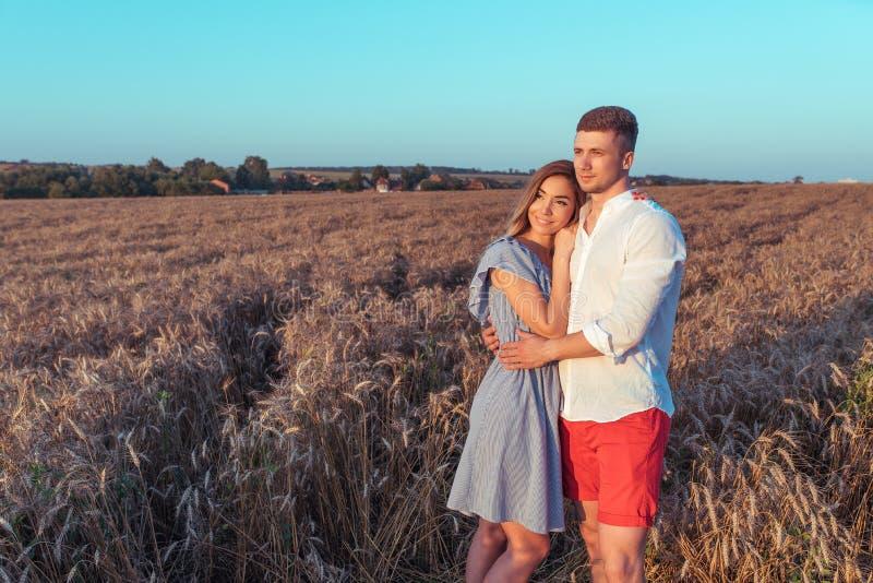 Pares, hombre y mujer jovenes en verano en el campo de trigo, abrazando y relajándose en aire fresco El concepto de amor es alegr imagen de archivo