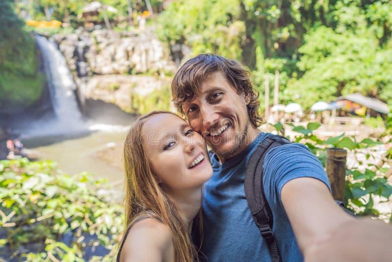 Pares, homem e mulher de sorriso fazendo o selfie em um fundo da cachoeira foto de stock royalty free