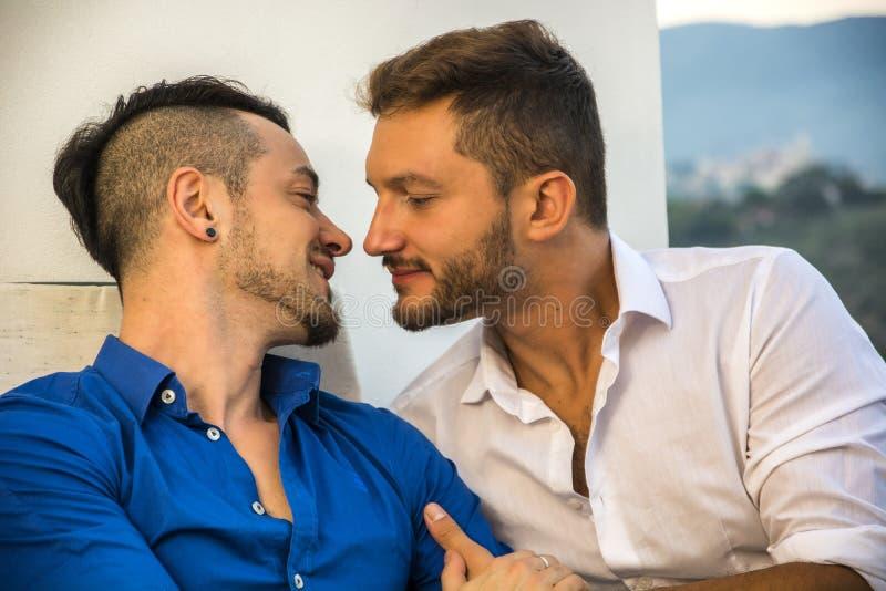 Pares homosexuales en sillas en el balcón fotografía de archivo libre de regalías