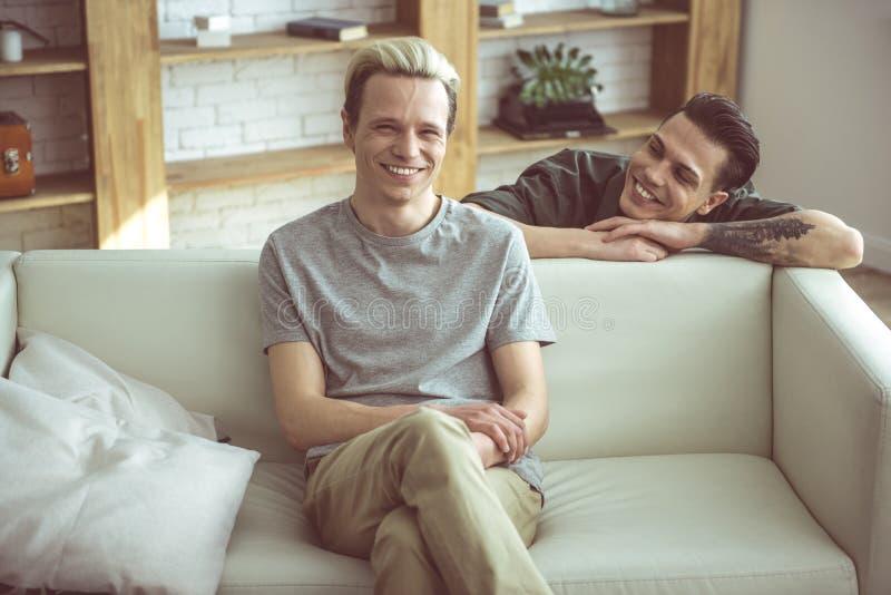 Pares homosexuales felices que pasan tiempo en casa fotografía de archivo
