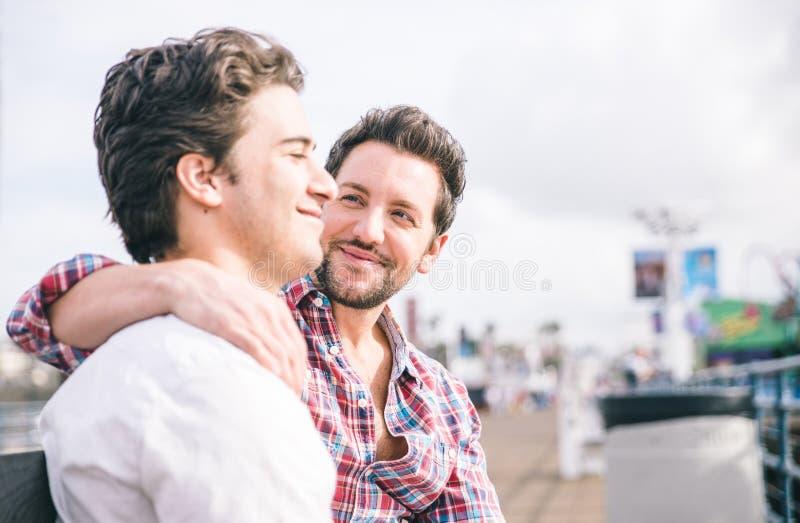 Pares homosexuales que se sientan en el embarcadero de Santa Mónica en un banco foto de archivo
