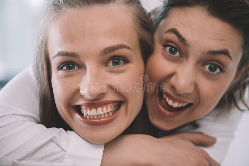 Pares homossexuais entusiasmado bonitos que abraçam e que sorriem imagem de stock