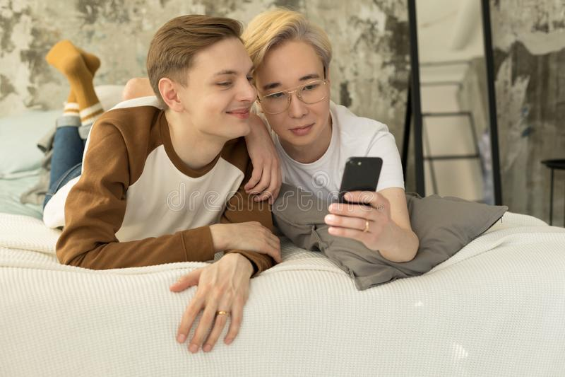 Pares homossexuais internacionais atrativos que relaxam na cama antes do sono da noite e que olham a tela do smartphone foto de stock
