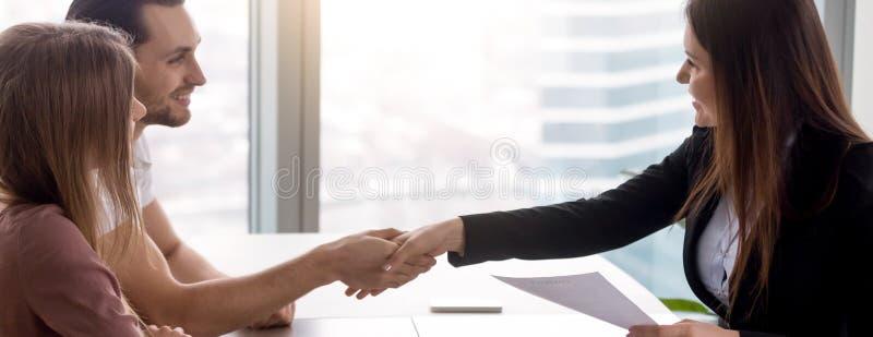 Pares horizontais da imagem que assinam o aperto de mão do contrato dos bens imobiliários com corretor de imóveis fotografia de stock