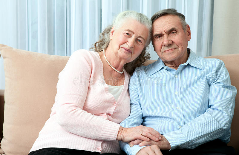 Pares idosos afetuosos com os sorrisos amigáveis de irradiação bonitos que levantam junto em um abraço próximo em sua sala de vis fotografia de stock royalty free
