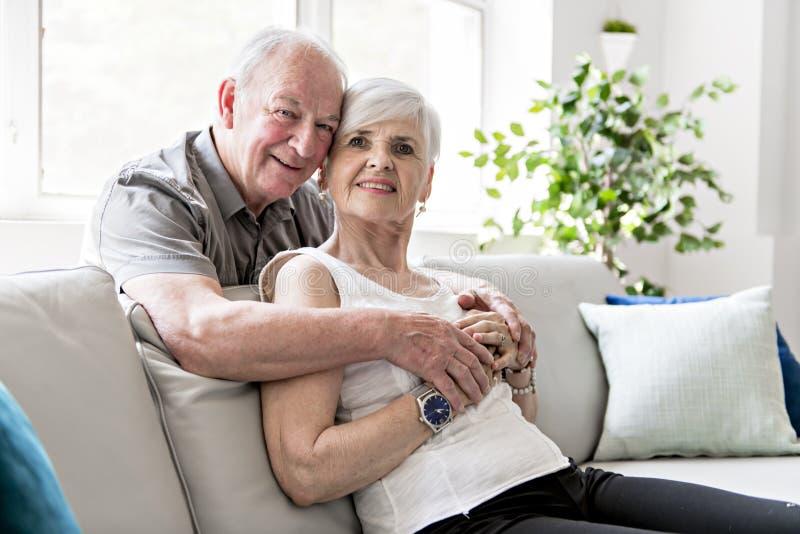 Pares idosos atrativos afetuosos que sentam-se junto em um sofá foto de stock royalty free