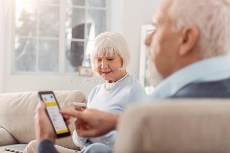 Pares idosos bonitos usando aplicações móveis em seus dispositivos fotos de stock