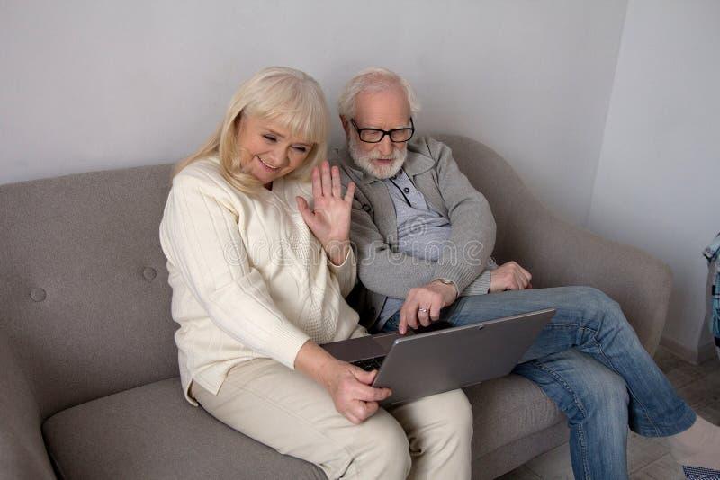 Pares idosos com o portátil no sofá fotos de stock