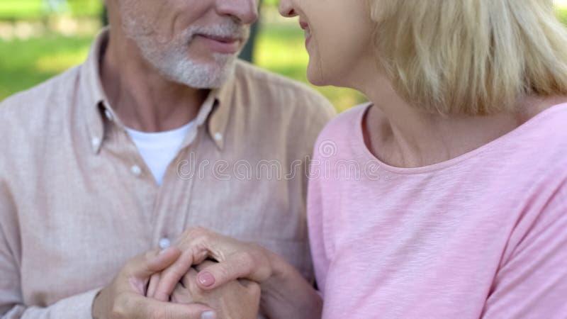 Pares idosos de amor que olham-se, o homem e a mulher guardando as mãos, afeição fotos de stock royalty free