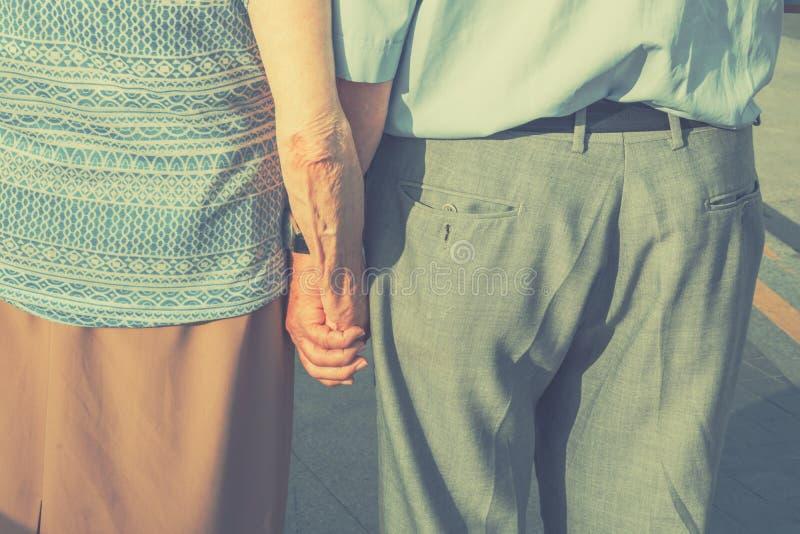 Pares idosos dos povos superiores que guardam as mãos que andam na rua Unidade romântica Fidelity da devoção do amor dos valores  imagem de stock royalty free