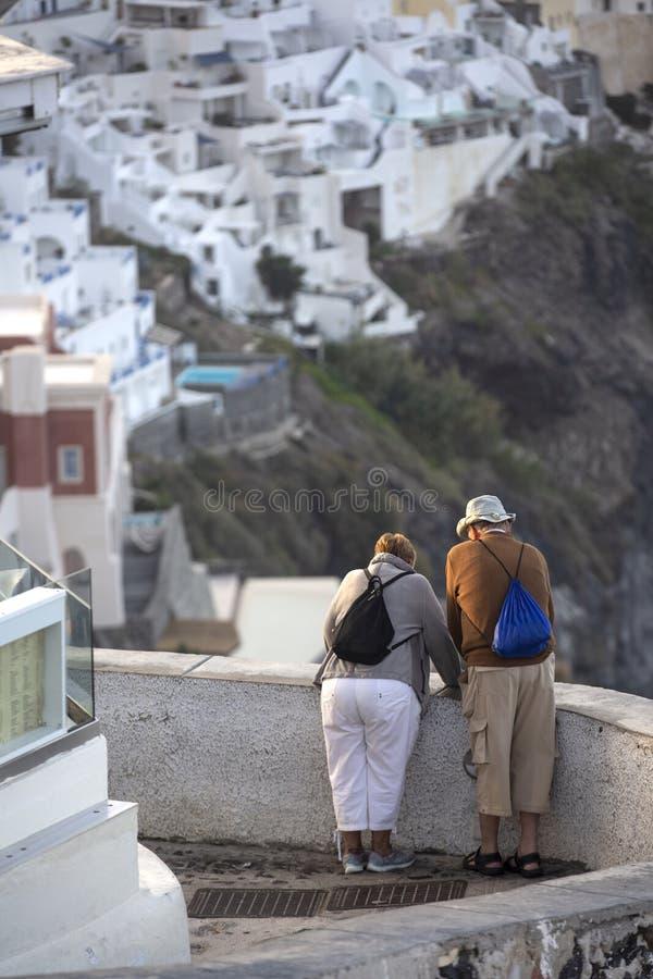 Pares idosos em Thira em Santorini Conceito do turismo, do curso e dos povos - par superior feliz imagem de stock