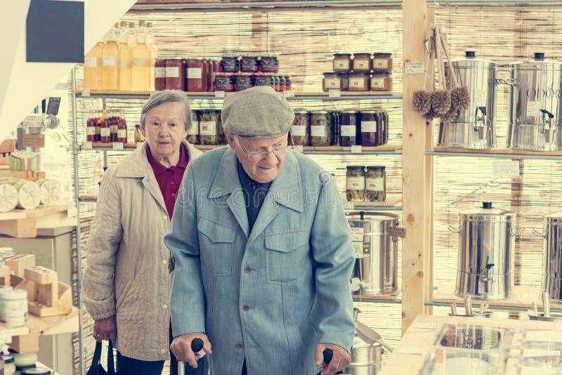 Pares idosos em uma compra zero do volume da loja do desperd?cio fotografia de stock