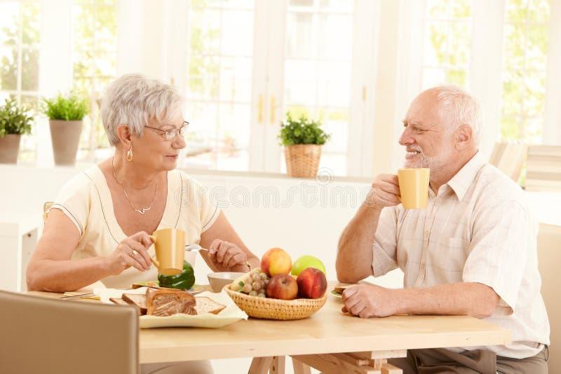 Pares idosos felizes que comem o pequeno almoço fotografia de stock