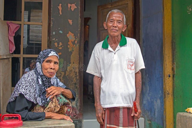 Pares idosos na roupa tradicional na frente de sua casa em Lombok, Indonésia fotografia de stock royalty free