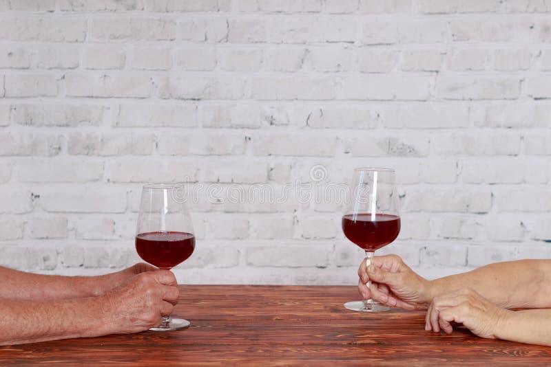 Pares idosos no vinho tinto dos testes do restaurante fotografia de stock royalty free