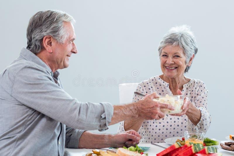 Pares idosos que comem o pequeno almoço imagens de stock royalty free