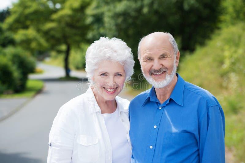Pares idosos que estão em uma estrada rural foto de stock