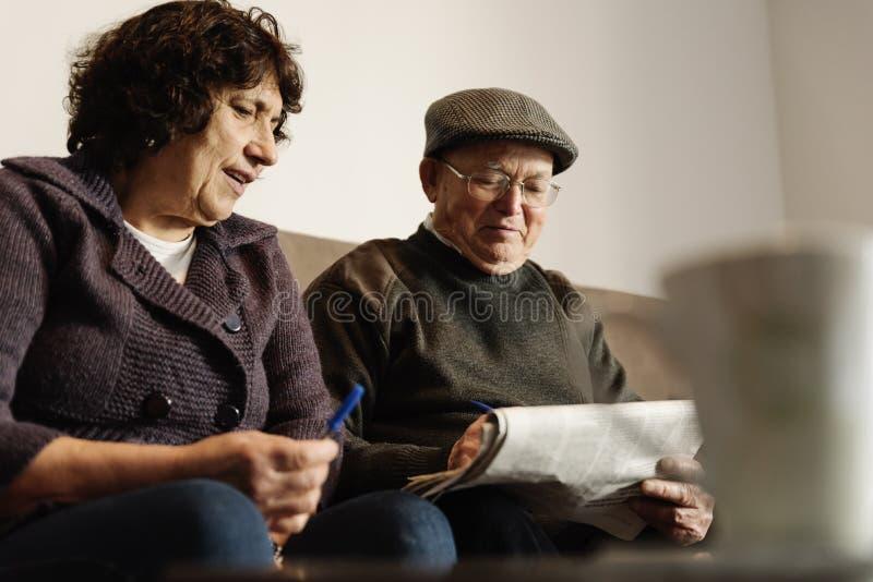 Pares idosos que leem um jornal imagens de stock royalty free