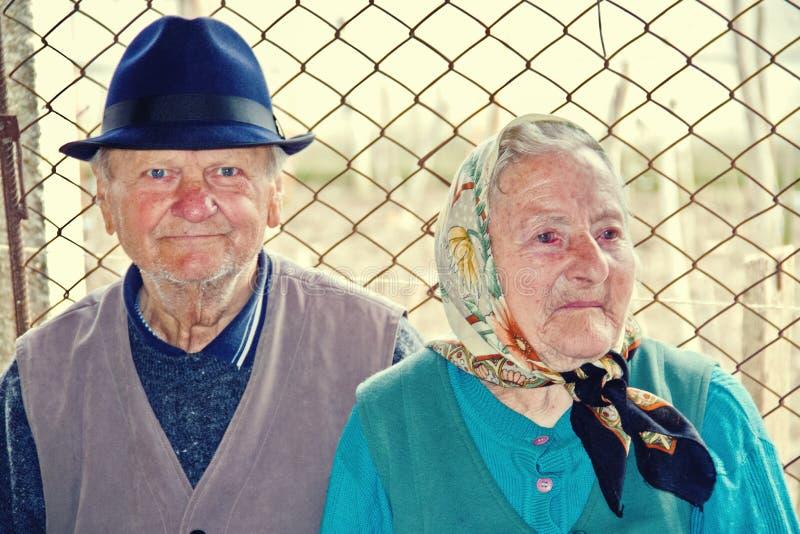 Pares idosos que sentam-se junto em uma estrada secundária foto de stock