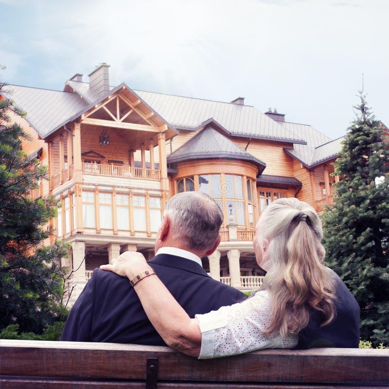 Pares idosos que sentam-se no banco no jardim perto da casa imagem de stock royalty free