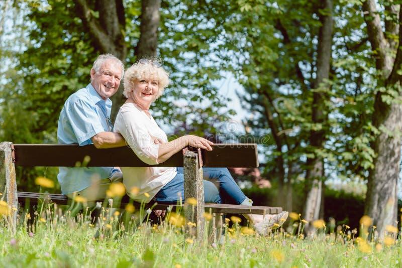 Pares idosos românticos que sentam-se junto em um banco em um dia tranquilo foto de stock