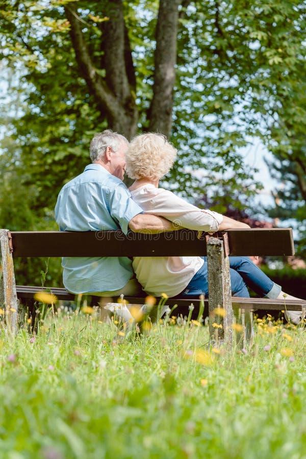 Pares idosos românticos que sentam-se junto em um banco em um dia tranquilo imagem de stock