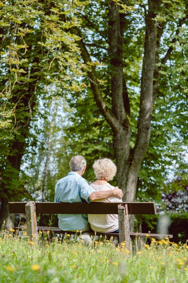 Pares idosos românticos que sentam-se junto em um banco em um tranqui imagem de stock royalty free