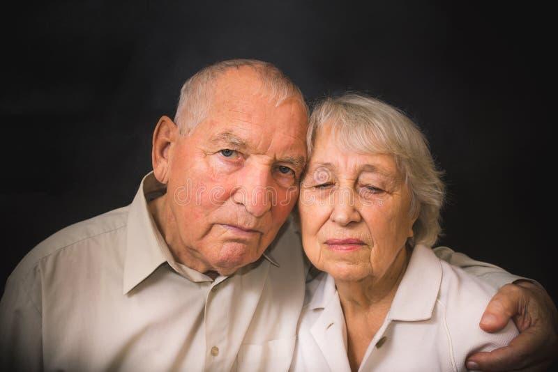 Pares idosos tristes em um fundo preto foto de stock royalty free