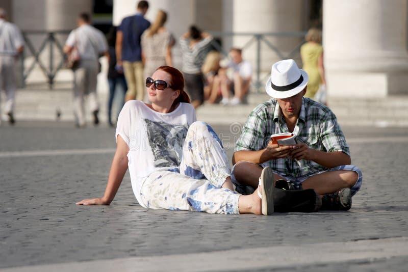 Pares indecisos dos turistas que olham um guia imagens de stock royalty free