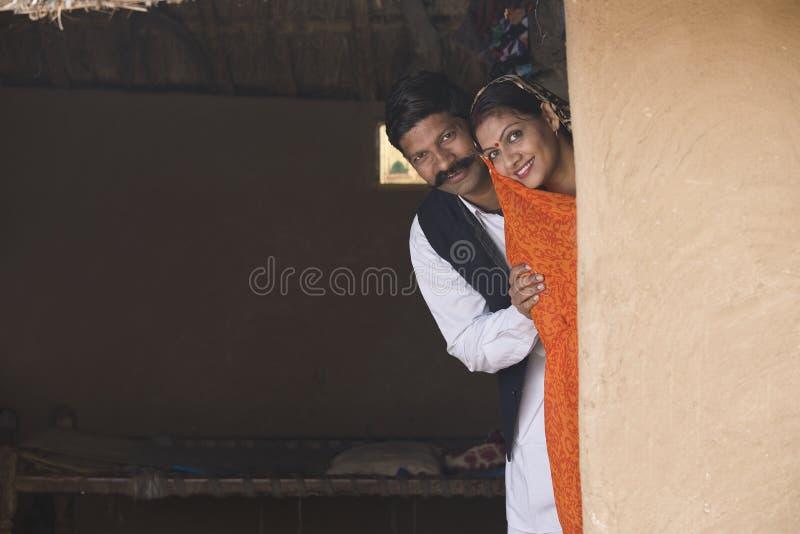Pares indianos felizes que espreitam da casa rural fotos de stock royalty free
