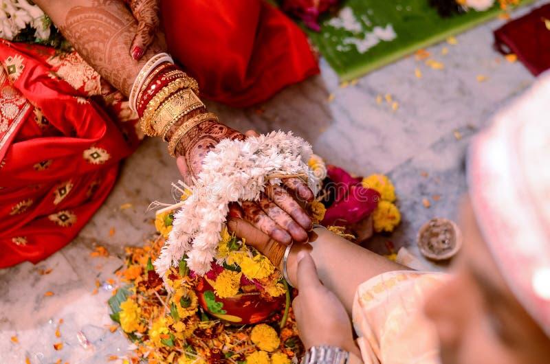 Pares indianos que guardam as mãos em seu ceremoney do casamento fotografia de stock