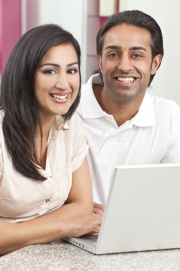 Pares indios asiáticos del hombre y de la mujer usando la computadora portátil fotografía de archivo