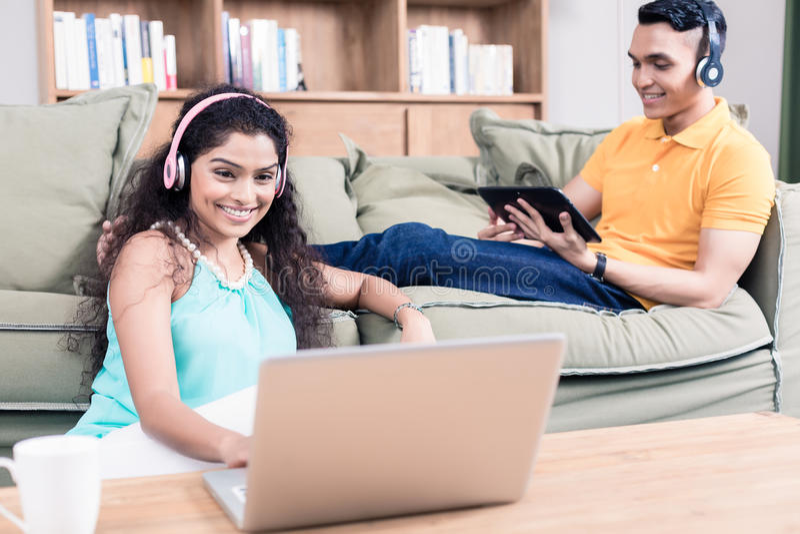Pares indios en su sala de estar usando el ordenador imagen de archivo