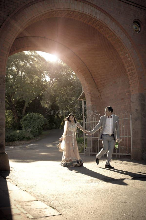 Pares indios felices jovenes que dan un paseo a través de arcada del ladrillo foto de archivo