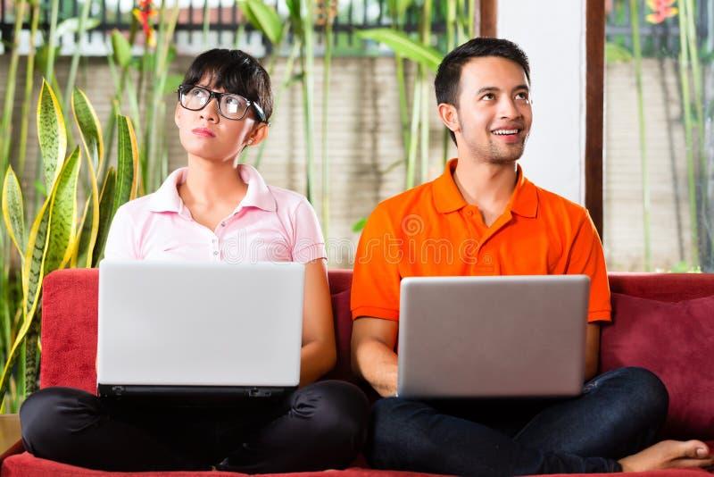 Pares asiáticos no sofá com um portátil imagem de stock royalty free