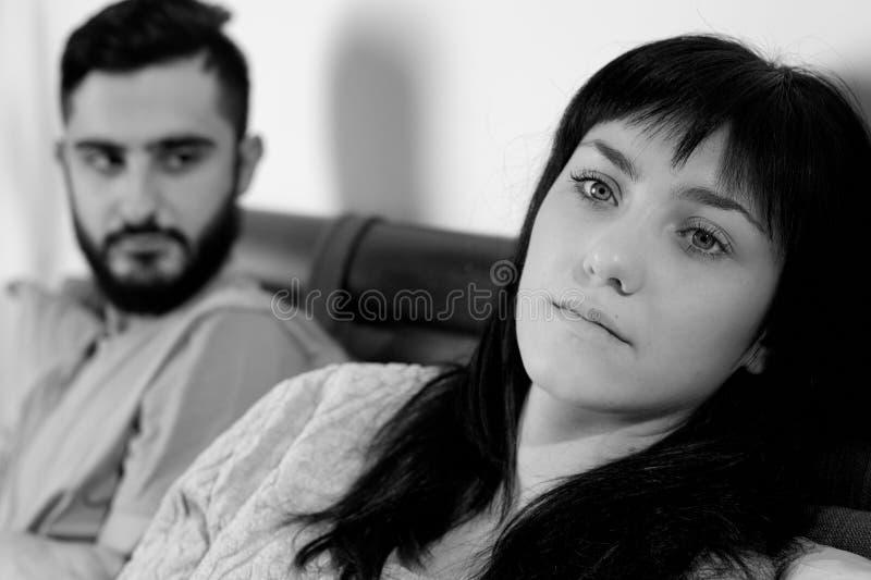 Pares infelices en la cama que lucha el primer triste blanco y negro fotografía de archivo libre de regalías