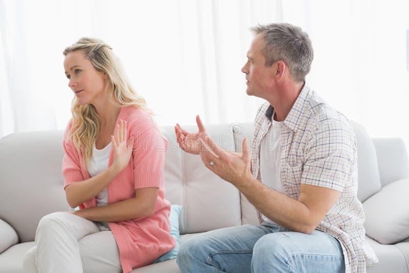 Pares infelices que discuten en el sofá foto de archivo libre de regalías
