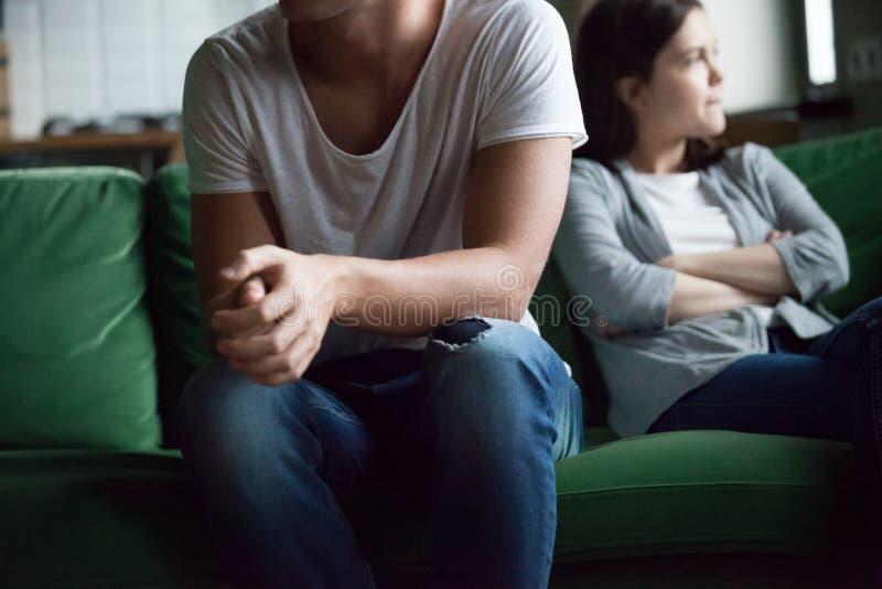 Pares infelices que se sientan en el sofá en casa fotografía de archivo