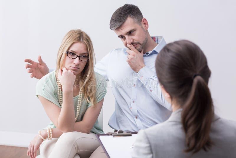 Pares infelizes casados jovens na sessão da psicoterapia fotos de stock