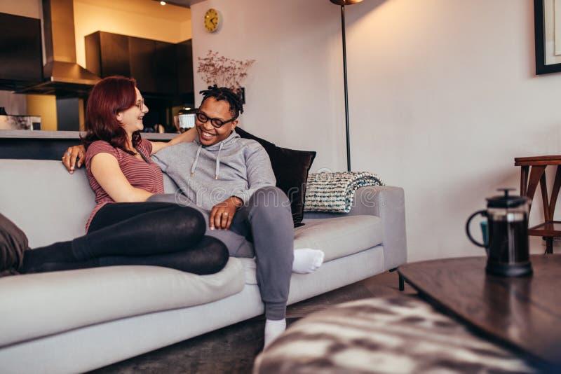 Pares inter-raciais alegres que relaxam no sofá imagem de stock
