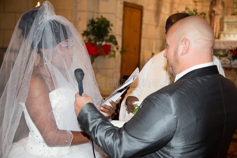 Pares inter-raciais caucasianos do homem e da mulher negra do casamento da raça misturada que trocam anéis na igreja da cerimônia foto de stock