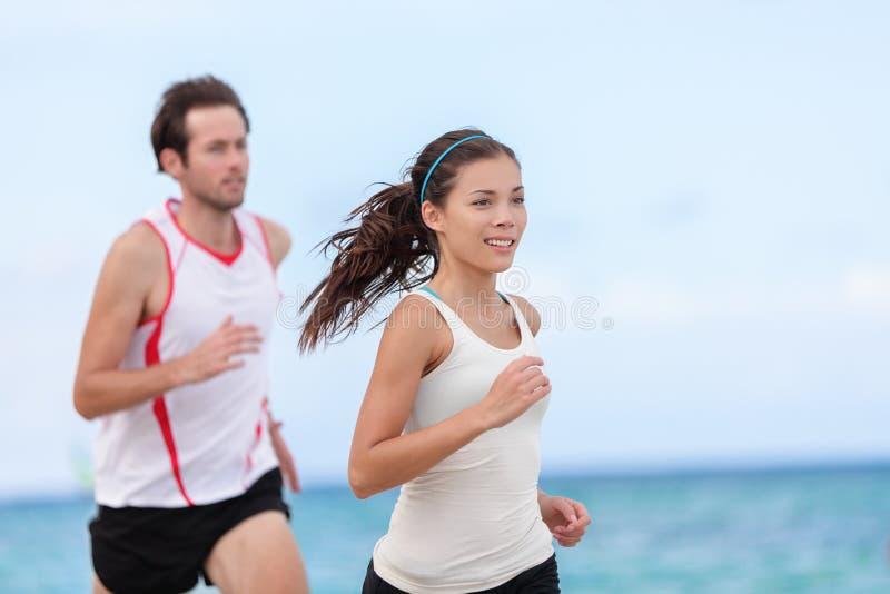 Pares inter-raciais do corredor da aptidão que correm na praia imagem de stock