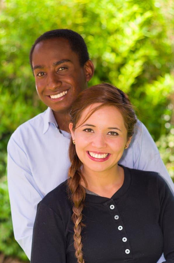 Pares inter-raciais novos bonitos no ambiente do jardim, abraçando e sorrindo felizmente à câmera foto de stock