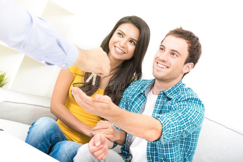 Pares inter-raciais novos que recebem chaves do mediador imobiliário foto de stock