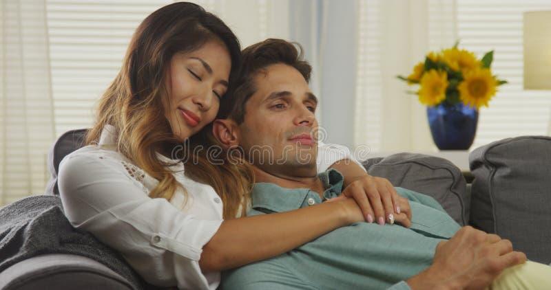 Pares inter-raciais que afagam no sofá fotos de stock royalty free