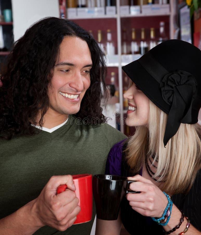 Pares inter-raciais que brindam com copos de café imagens de stock