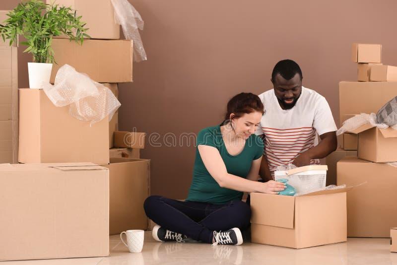 Pares inter-raciais que desembalam caixas dentro Mover-se na casa nova fotografia de stock