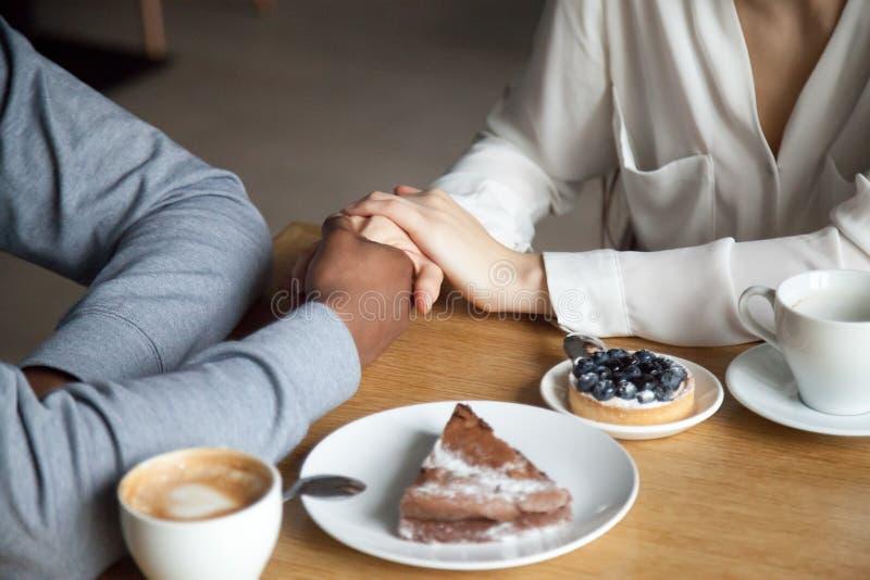 Pares inter-raciais que guardam as mãos que sentam-se na tabela do café, close up imagens de stock royalty free